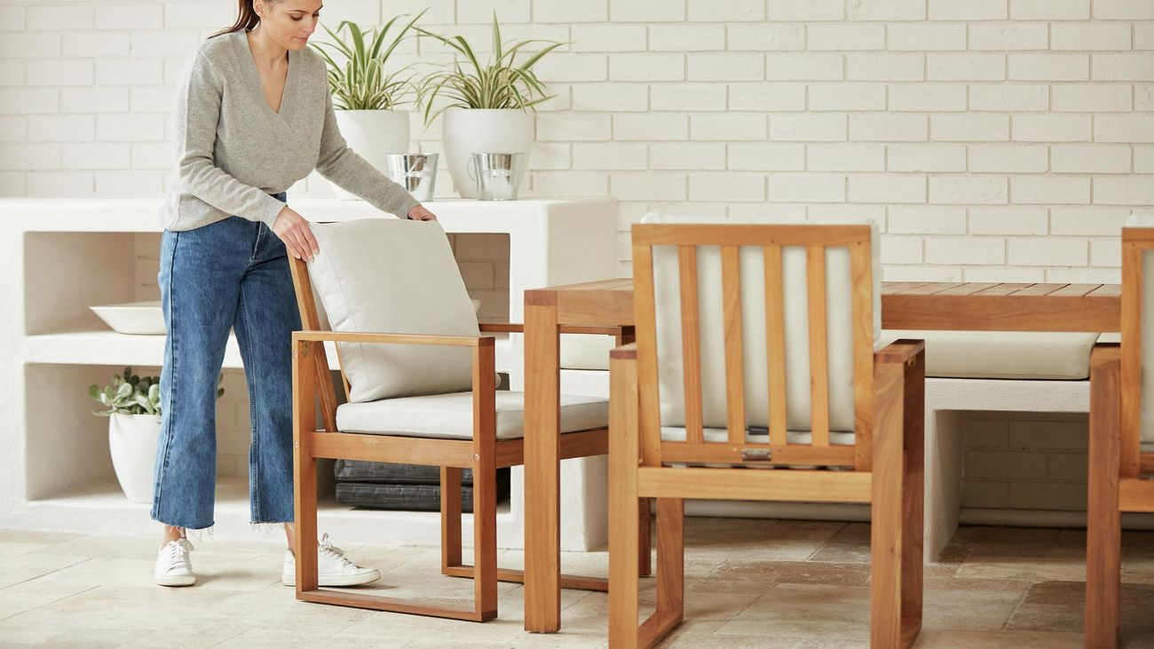 Woman adjusts a timber outdoor dining chair