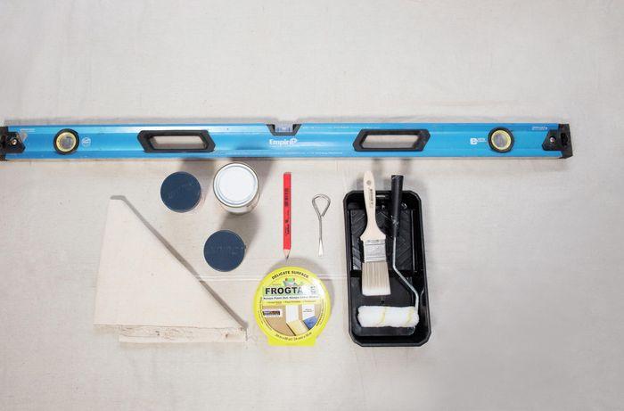 Spirit level, paint, drop sheet, paint brush and roller, paint try.