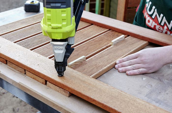 Person using a fixing gun on timber.