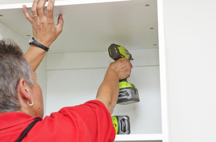 A Bunnings team member screwing the cabinet into place.