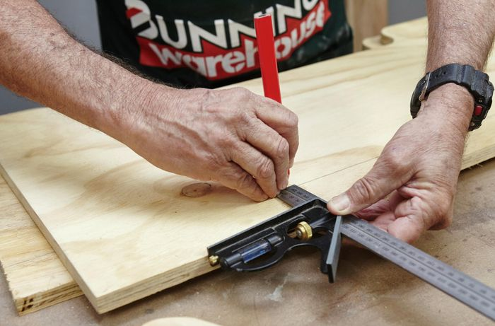 Person measuring and marking ply panel with ruler and pencil