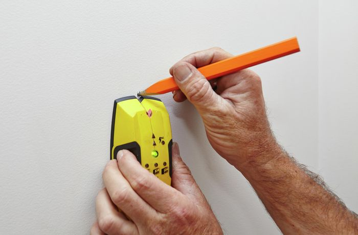 Marking the location on the wall with a pencil.