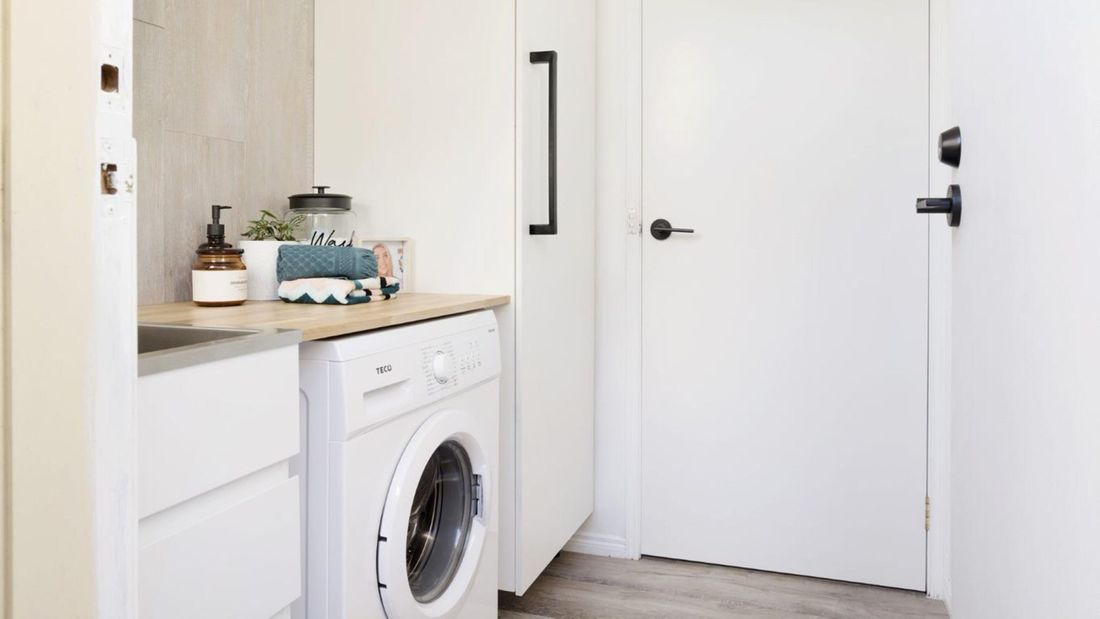 Renovated laundry with white goods and timber benchtop.
