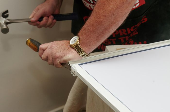 A person using a hammer and chisel to remove door guides from a mirror door