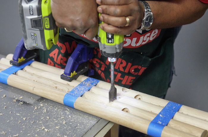 A drill bit being used to cut holes for a support rail in bar stool legs