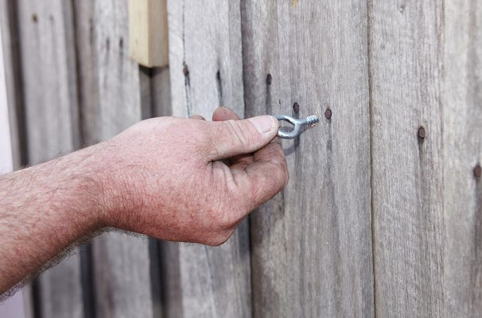 A person screwing a hook eye into a paling fence