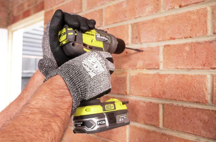 Person drilling into brick wall.