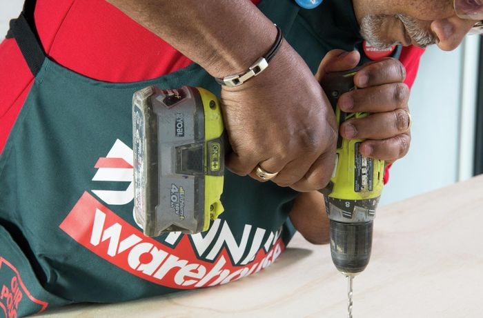 Person drilling hole for anchor point into timber