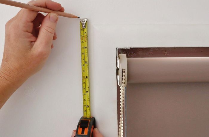 A pair of hands marking a window frame to install curtain brackets
