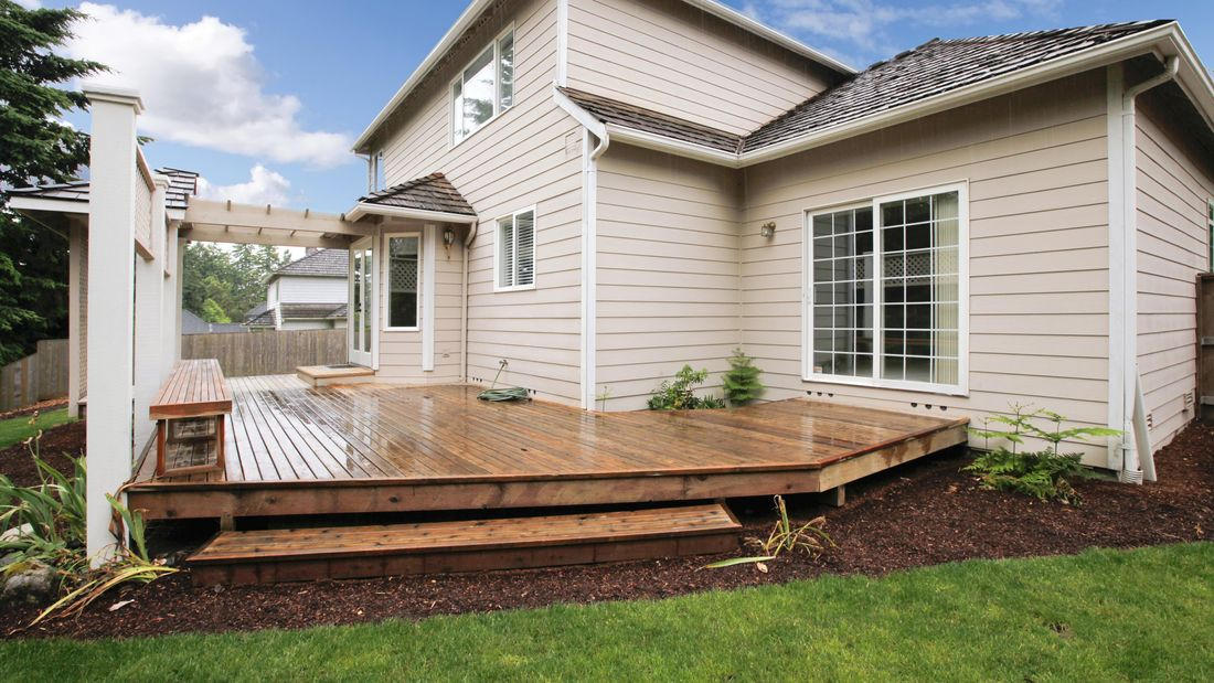 Two-storey weatherboard house with outdoor deck and garden