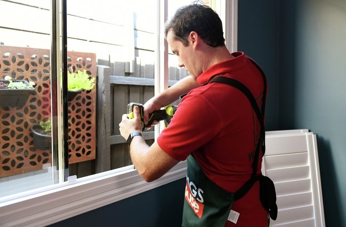 Person using cordless drill to attach plantation shutter frame to window frame