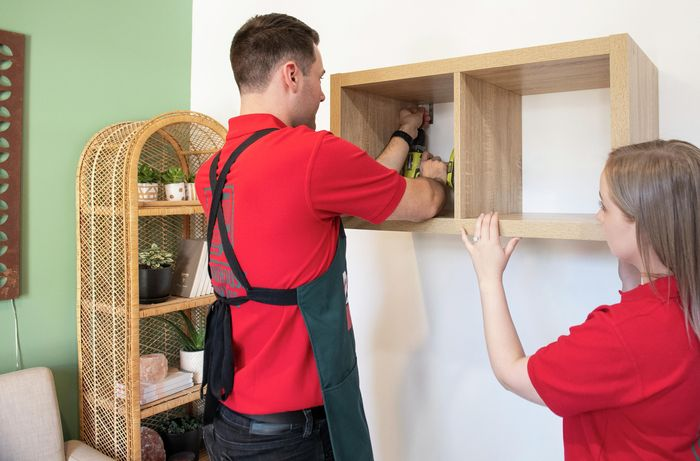 A cube shelf being screwed into a white wall by two Bunnings team members