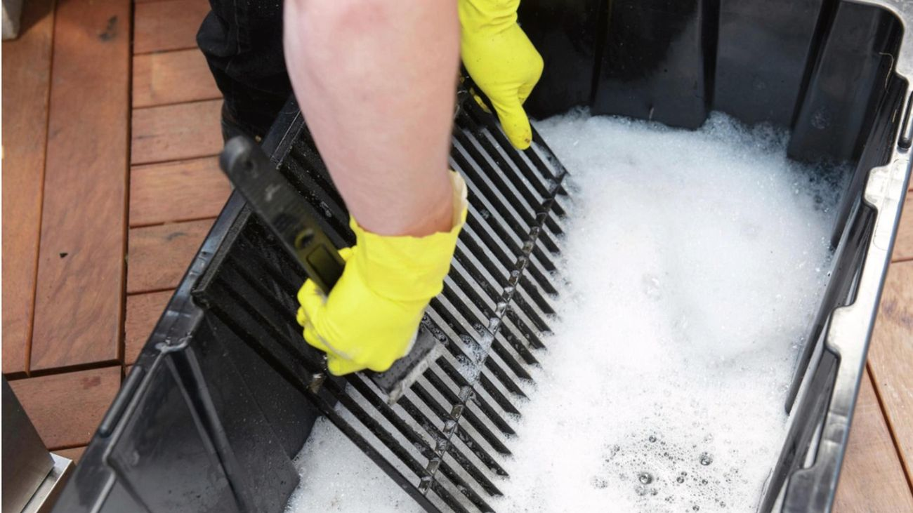 A person wearing gloves scrubbing a barbecue grill in soapy water