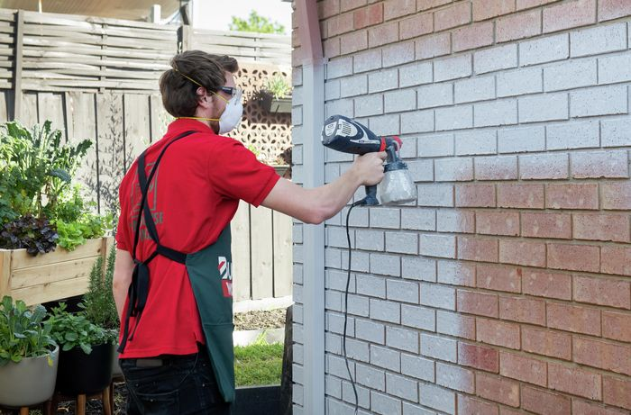 Person using spray gun with gray paint on brick wall.