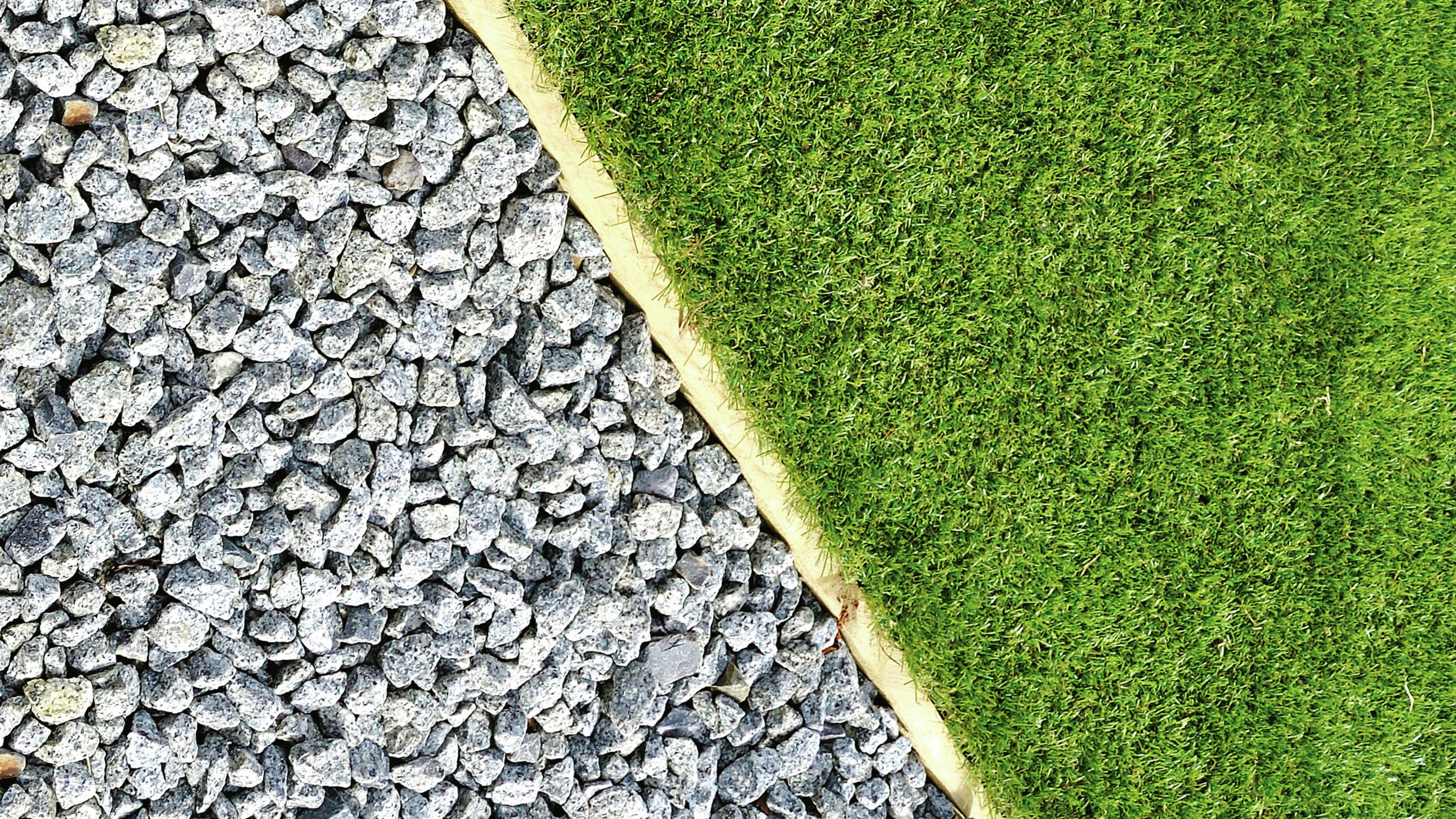 Gravel, pebbles and grass separated by retaining wall.
