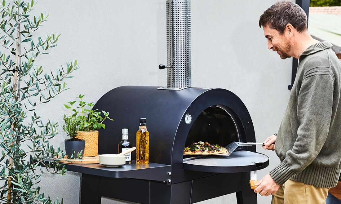 Pizza oven being used by man
