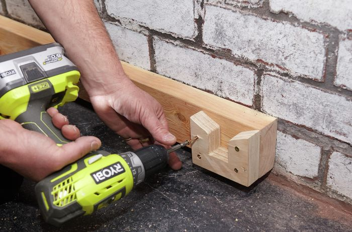 Person attaching bracket to timber.