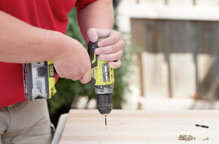 A Bunnings team member pre-drilling a piece of timber