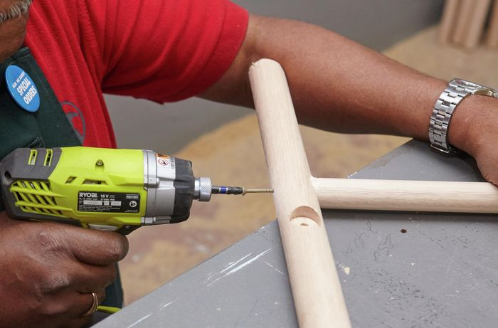 Stool legs being drilled to secure a foot rail