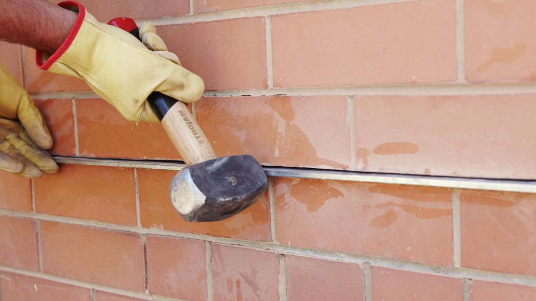 A person using a rubber mallet to insert a metal lintel into a slot in brickwork