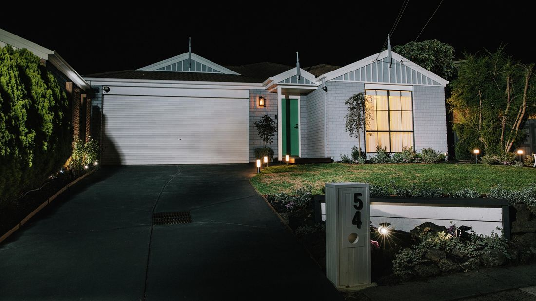 A pale blue brick house shot from the street, with garden lights throughout the yard