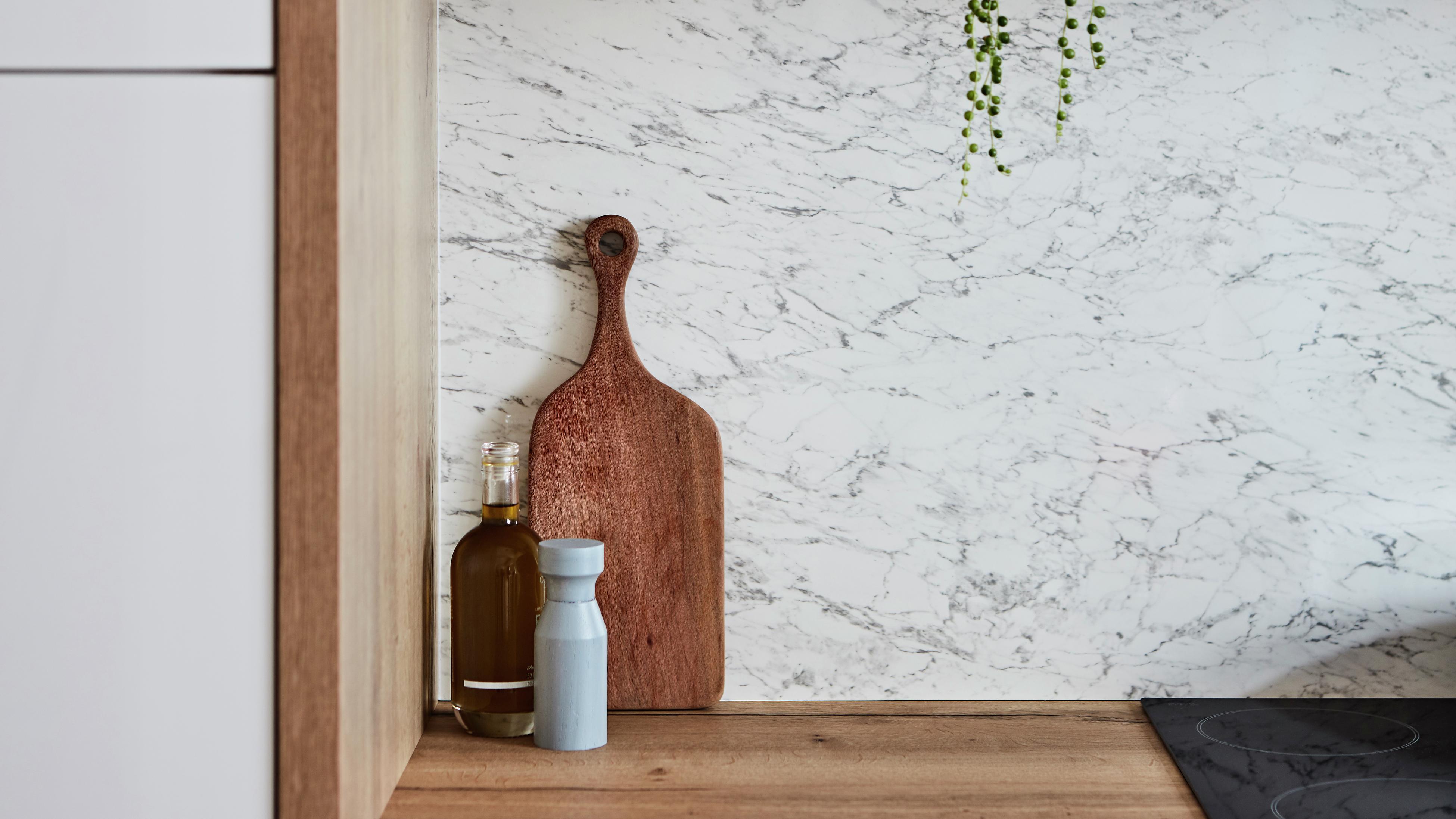 Bottle of oil, salt shaker and wooden serving platter sitting on top of wooden benchtop.