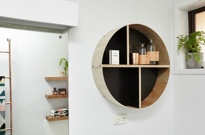 A round shelf unit containing decorative bottles and perfume