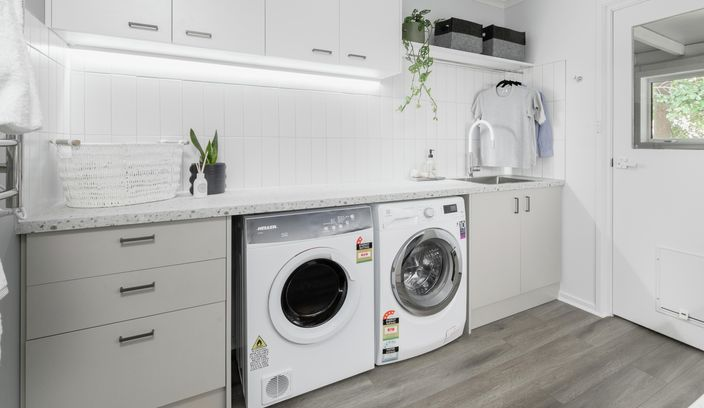 Laundry with washer, drying and storage cupboards.