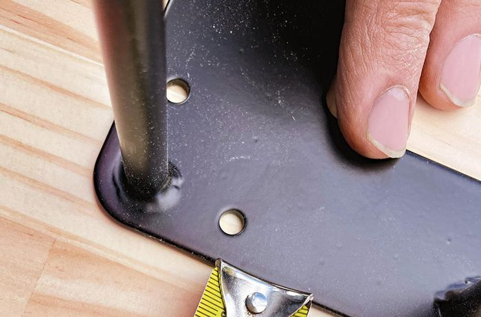 A person measures, positions and secures hairpin legs to a dining table