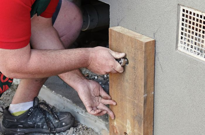 Person using ratchet and bolt to secure support post against the wall.