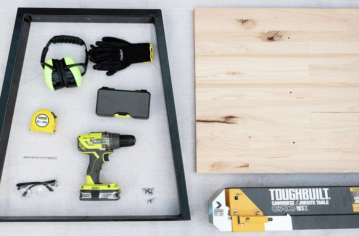 Earmuffs, gloves, level, measuring tape, drill, drill bits, safety glasses, timber and ladder laid out on the ground.
