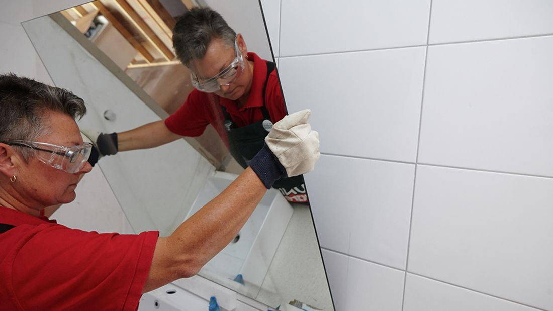 Bunnings team member placing a large mirror against a white tile wall in a bathroom