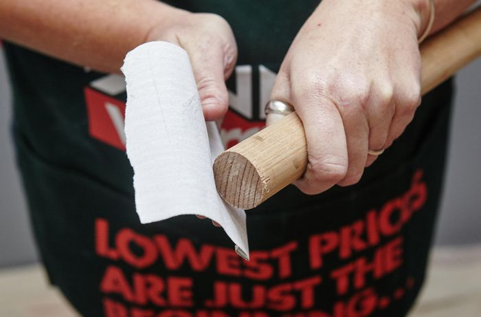 Person sanding timber dowel.