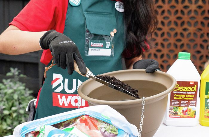 Bunnings Team Member using a spade to pour soil into a large pot