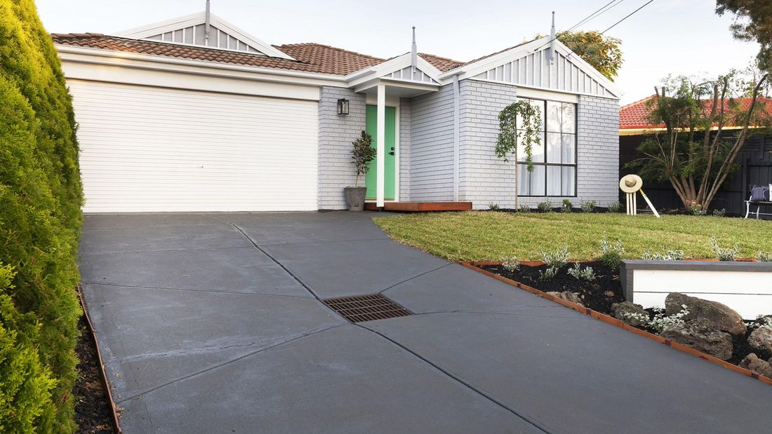 Exterior of brick house painted grey with a concrete driveway.