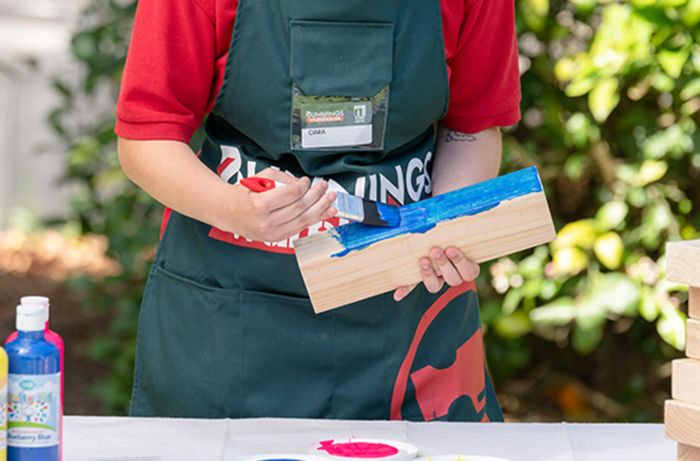 Bunnings team member painting a piece of timber with blue paint