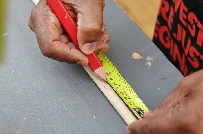 Person measuring and marking timber with tape measure and pencil