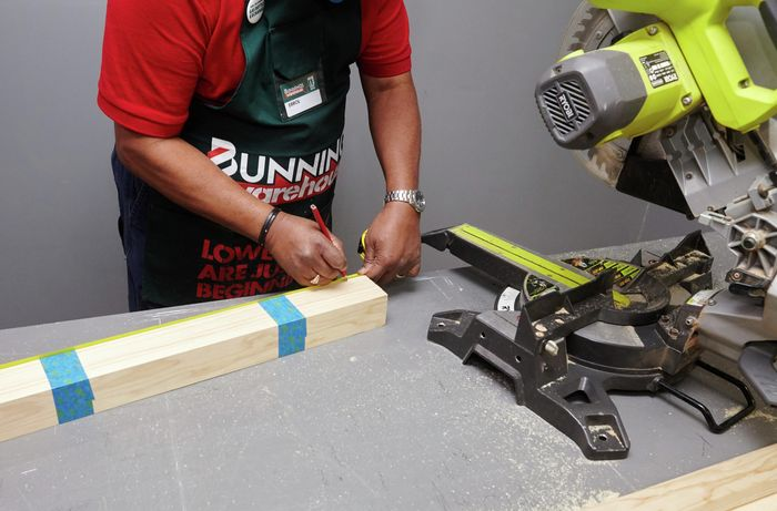 A person measuring lengths of pine timber taped together