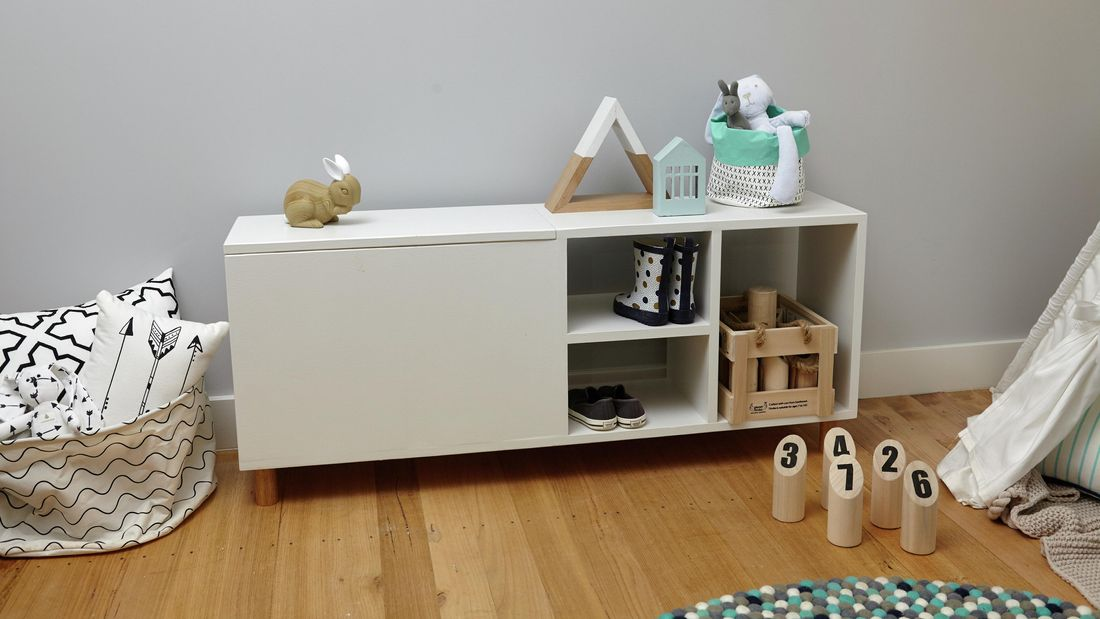 A completed wooden storage bench for children, holding shoes, boots, a toy crate, a toy rabbit and more