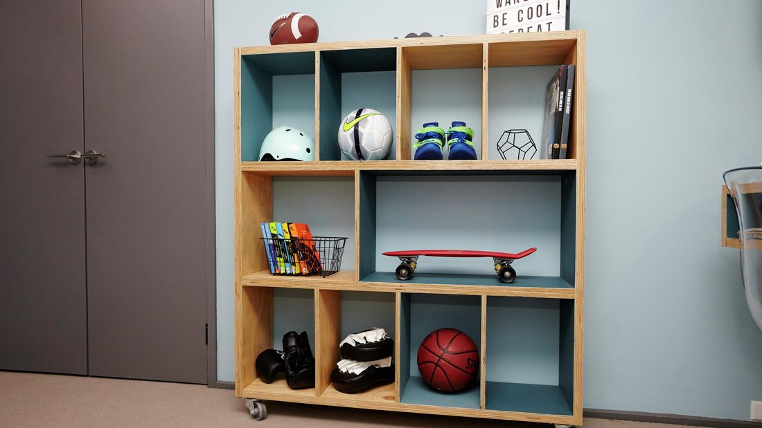 A completed cube storage unit on castor wheels, carrying a helmet, soccer ball, shoes, books, skateboard, boxing gloves, basketball, football and more