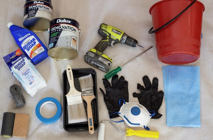 Sugar soap, laminate paint, drill, screwdriver, bucket, cloth, safety equipment, sanding blocks and painting gear all laid out.