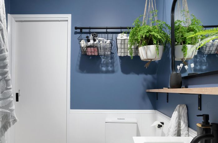 A completed bathroom storage basket rail in a blue themed bathroom with a hanging plant
