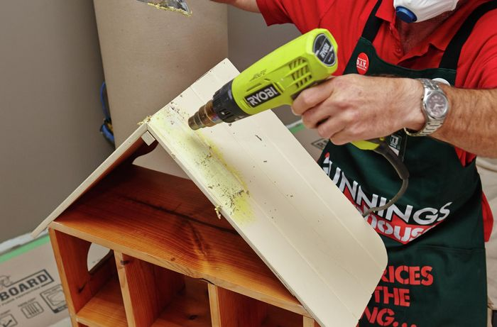 A heat gun being used to peel away paint from a bevelled roof of a wooden frame