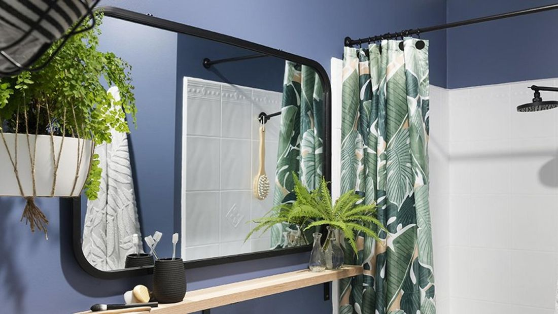 A bathroom with a curved edge mirror, hanging plant and colourful show curtain