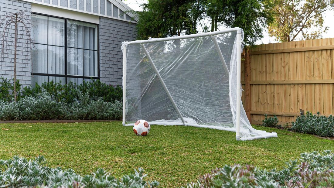 diy soccer goal in front yard of house with soccer ball on lawn