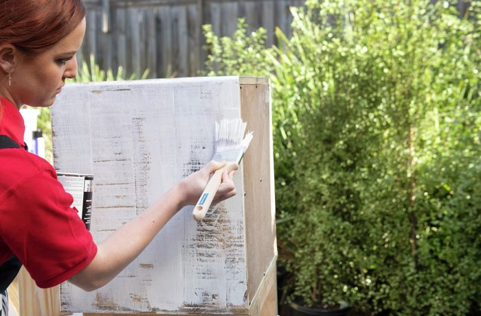 Woman painting a wooden bedside table with white paint
