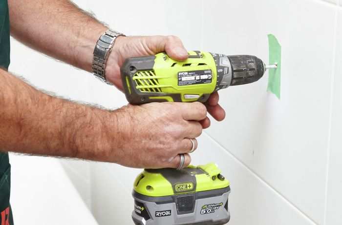 A person drilling into a tile wall marked with masking tape