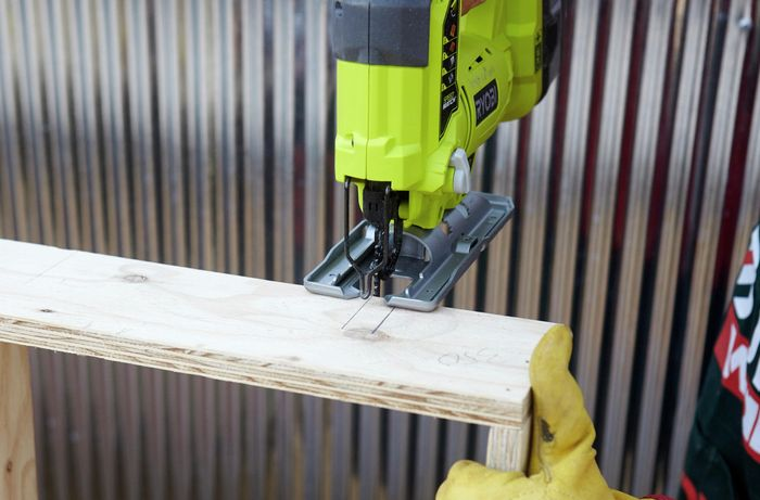 Person using jigsaw to cut slits in timber