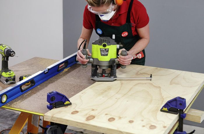 A person cutting a circle in plywood using a router