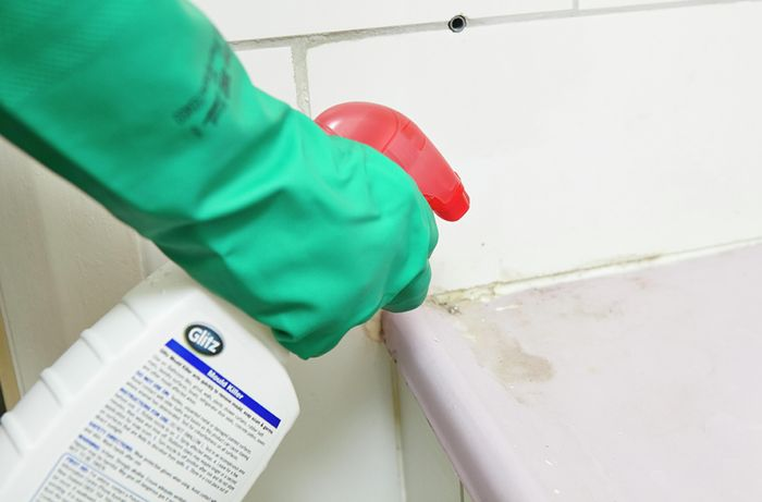 A person wearing rubber gloves spraying a line of grout using a spray bottle